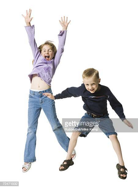 portrait of a boy jumping with his sister - legs apart stock pictures, royalty-free photos & images