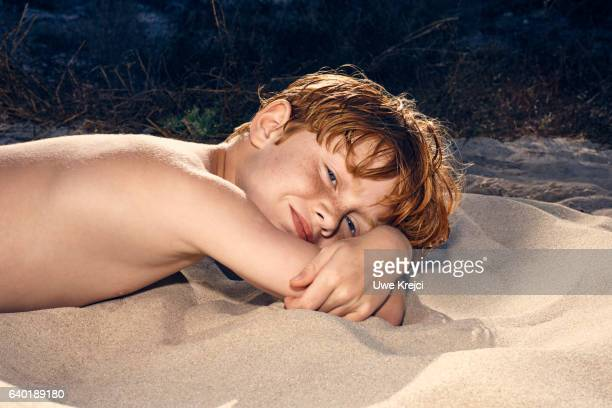 Portrait of a boy laying in the sand on beach