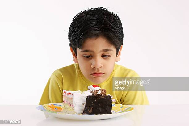 Portrait of a boy looking sadly at pastries served in a plate