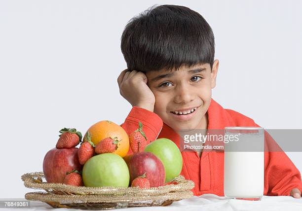 Portrait of a boy making a face in front of a glass of milk and a basket of fruits