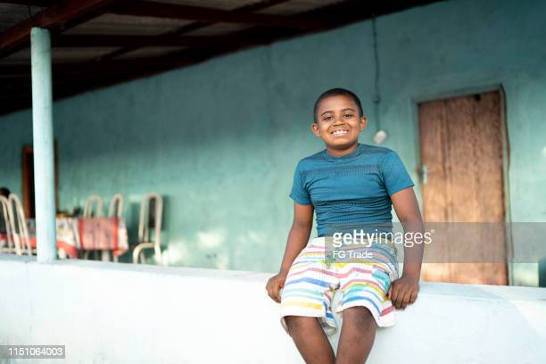 portrait of a boy outdoors in a rural scene sitting in a small wall - humility stock pictures, royalty-free photos & images