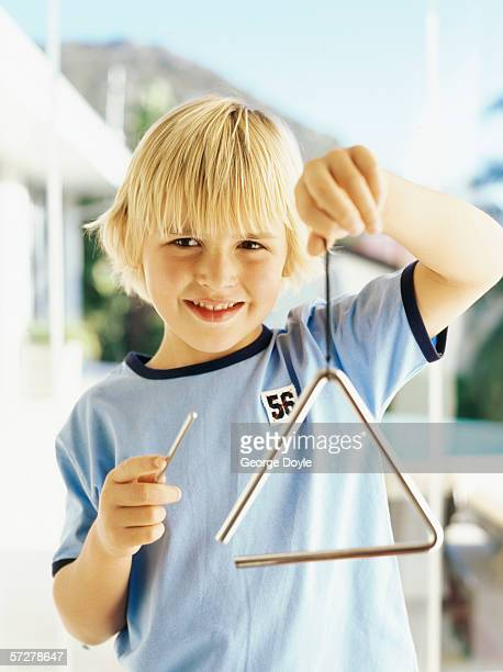 Portrait of a boy playing a triangle