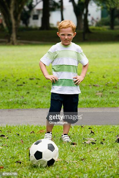 portrait of a boy playing soccer in a park - arms akimbo stock pictures, royalty-free photos & images