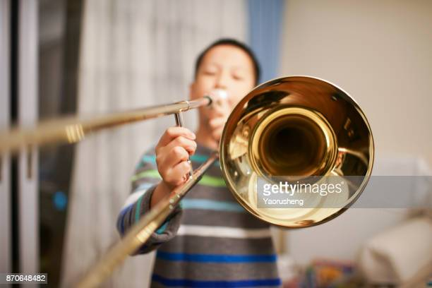 portrait of a boy playing the trombone - instrumento musical - fotografias e filmes do acervo