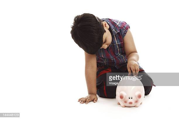 Portrait of a boy putting a coin into a piggy bank