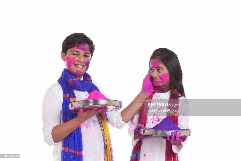Portrait of a boy putting holi colour on a girl : Stock Photo