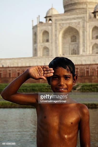 Portrait of a boy saluting in front of a mausoleum Yamuna River Taj Mahal Agra Uttar Pradesh India