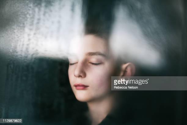 portrait of a boy shot through a window