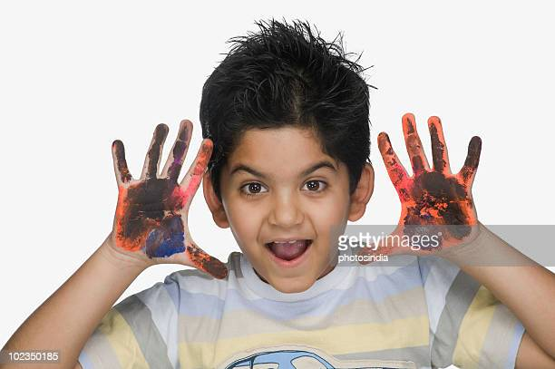 Portrait of a boy showing his painted hands