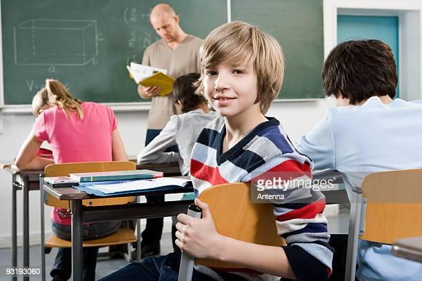 Portrait of a boy sitting in a classroom