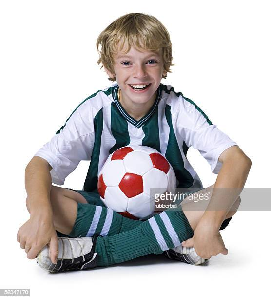 Portrait of a boy sitting with a soccer ball