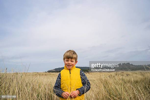 Portrait of a boy standing in tall grass by beach