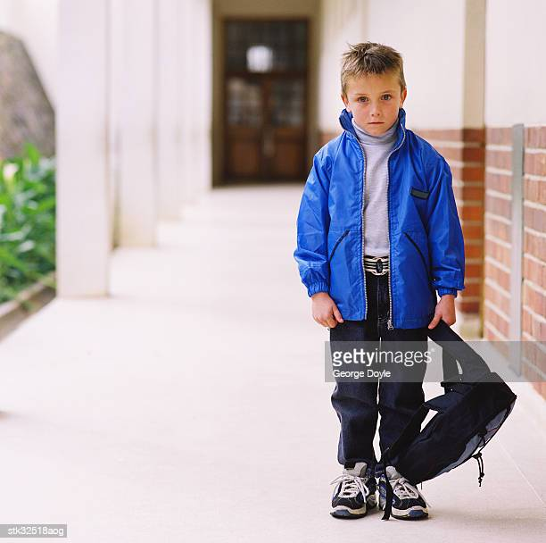 portrait of a boy (6-8) standing with a bag in the school corridor