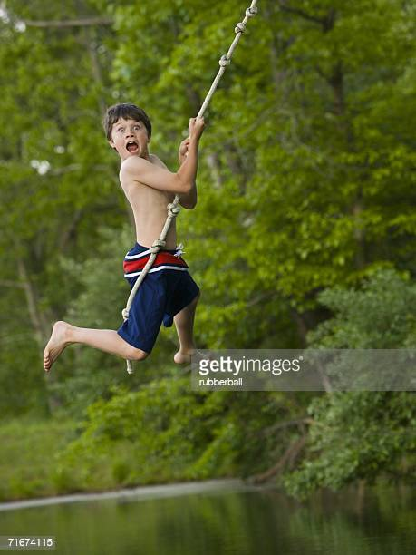 Portrait of a boy swinging on a rope
