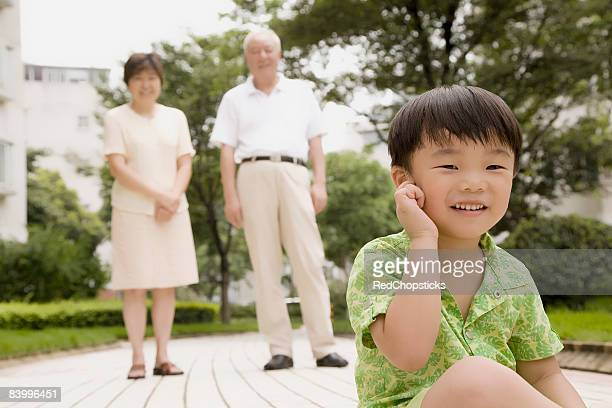 Portrait of a boy touching his ear with his grandparents standing behind him