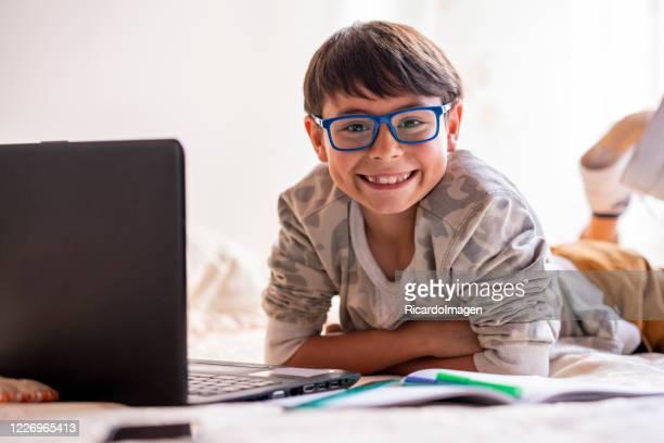 retrato de um menino assistindo a câmera enquanto faz seu dever de casa de sua cama em sua casa em quarentena - 6 7 anos - fotografias e filmes do acervo