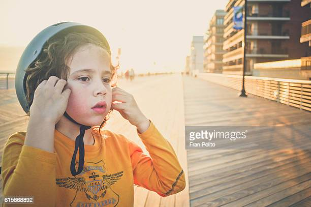 Portrait of a boy wearing a bicycle helmet on the boardwalk.