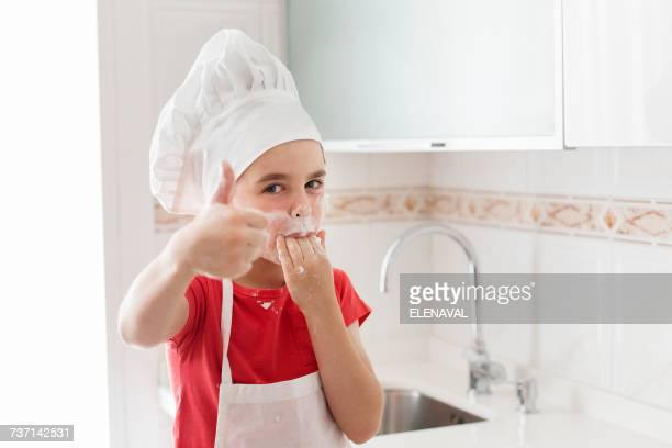 Portrait of a boy wearing a chefs hat licking his fingers