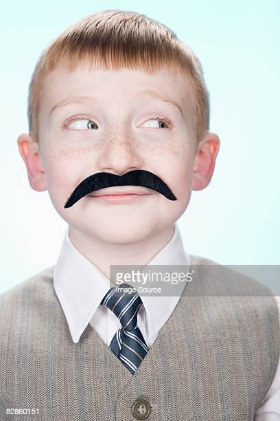 Portrait of a boy wearing a fake moustache