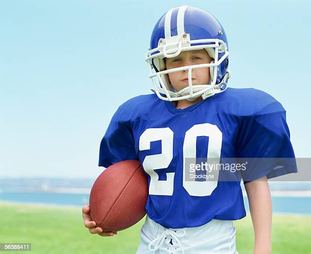 portrait of a boy wearing a helmet holding a football - american football strip stock pictures, royalty-free photos & images