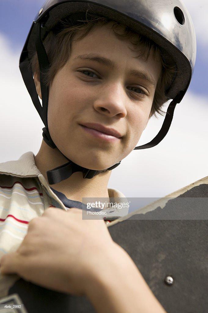 Portrait of a boy wearing a helmet holding a skateboard : Foto de stock