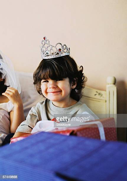 portrait of a boy (6-8) wearing a tiara and smiling