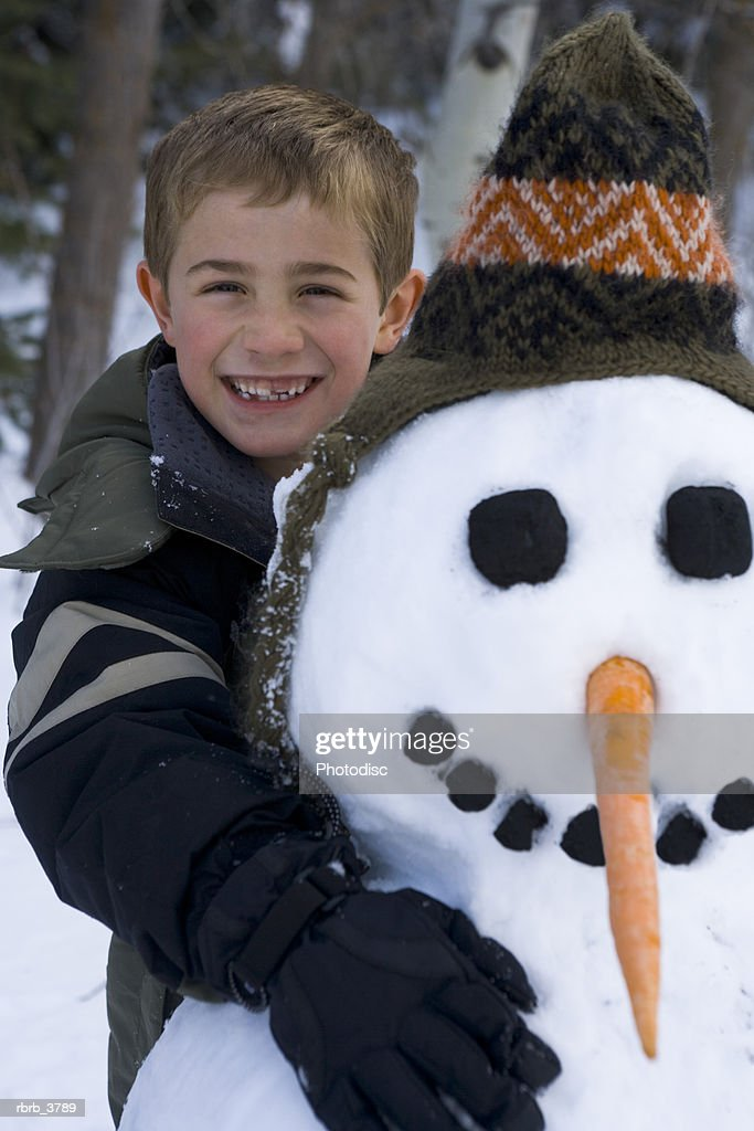 Portrait of a boy (6-7) with a snowman : Foto de stock