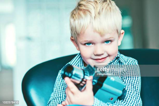 Portrait of a boy with an old video camera