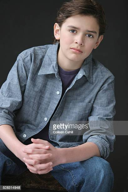 Portrait of a boy with brown hair and brown eyes wearing a denim shirt with hands clasped; troutdale oregon united states of america