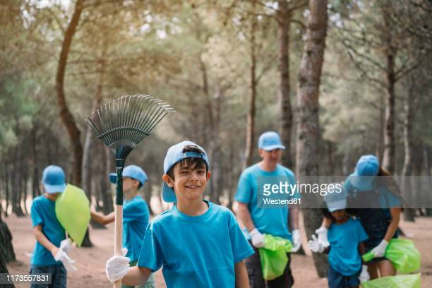 portrait of a boy with group of people collecting garbage in a park - kids with cleaning rubber gloves stock pictures, royalty-free photos & images