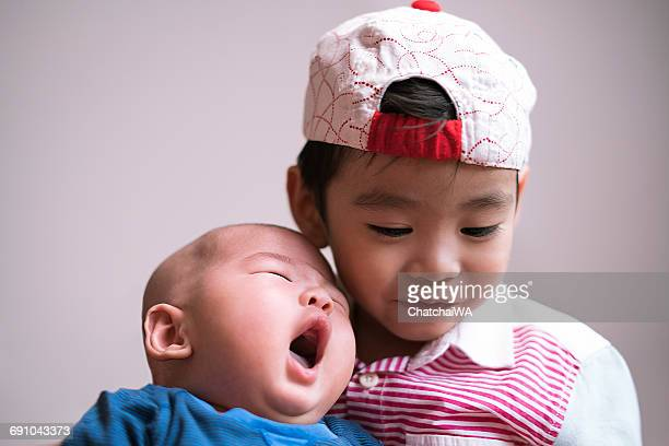 portrait of a boy with his baby brother yawning - 2 5 mesi foto e immagini stock