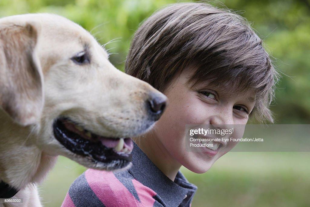 Portrait of a boy with his dog in foreground : Stock Photo