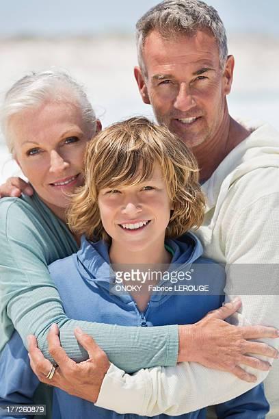 portrait of a boy with his grandparents on the beach - onoky stock-fotos und bilder