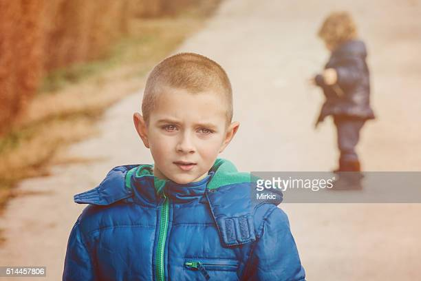 Portrait of a boy with his sister in the background