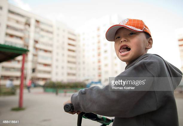Portrait of a boy with tooth decay in front of prefabricated concrete apartment blocks on August 19 in Ulan Bator Mongolia Social housing apartments...