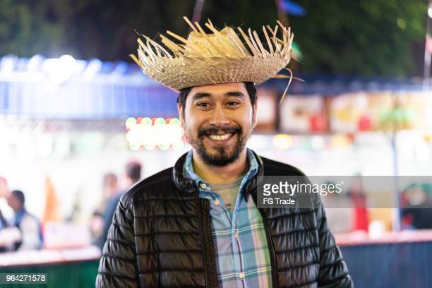 portrait of a brazilian man in the junina party at night (festa junina) - caipira style - straw hat stock pictures, royalty-free photos & images