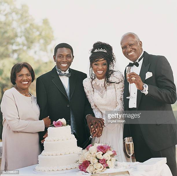 Portrait of  a Bride and Groom With a Senior Couple, Cutting the Cake at a Wedding Reception