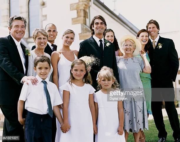 Portrait of a Bride and Groom With their Family Standing Outside of a Church