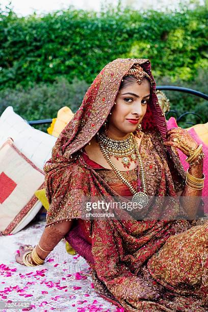 Portrait of a bride in a traditional wedding dress sitting on the bed in a lawn
