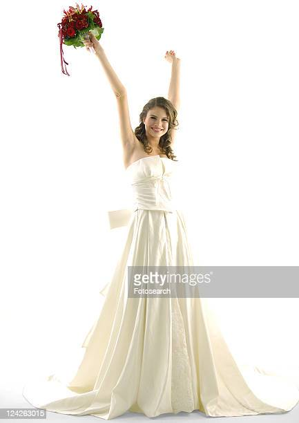 Portrait of a bride raising her arms and smiling