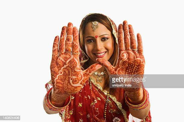 Portrait of a bride showing henna decorated palms