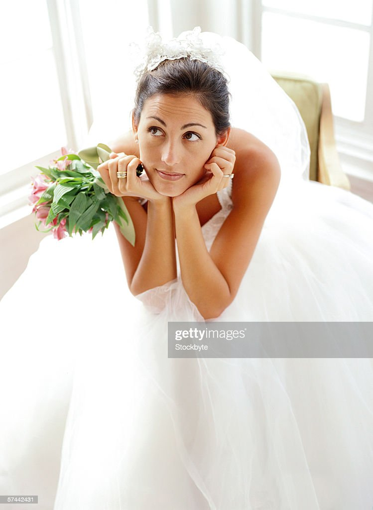 portrait of a bride sitting and leaning forward with a bouquet of flowers : Stock Photo