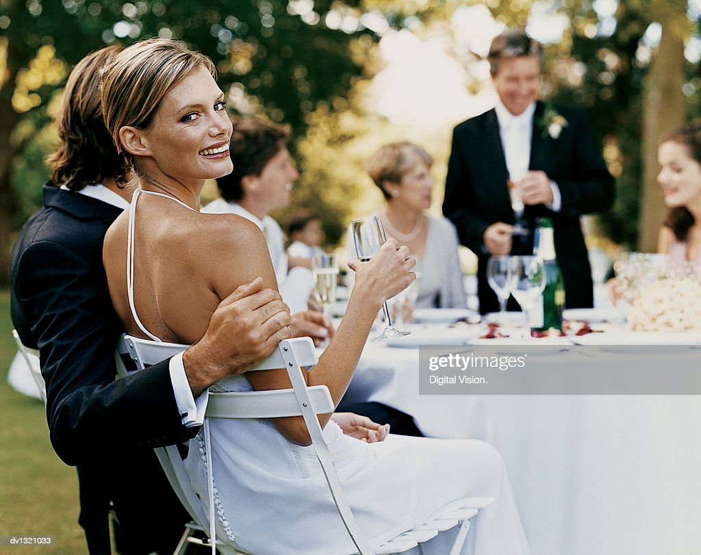 Portrait of a Bride Sitting at a Wedding Reception in a Garden With a Glass of Champagne : Stock Photo