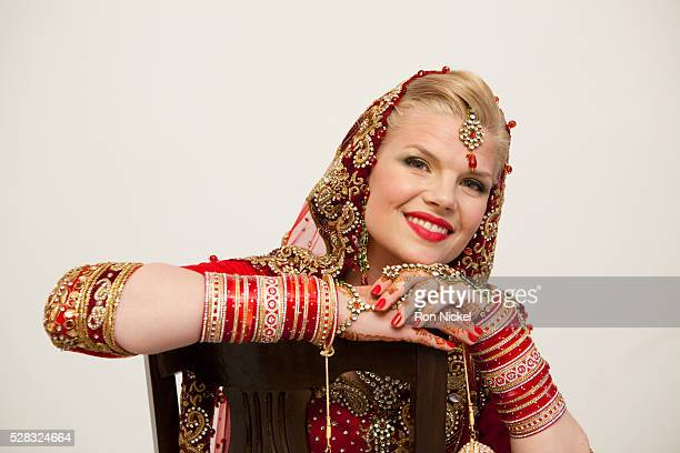 Portrait of a bride with blond hair wearing a red and gold sari and jewelry; ludhiana punjab india
