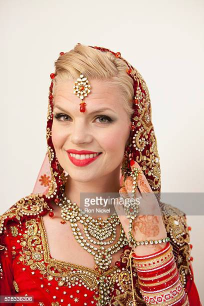 Portrait of a bride with blond hair wearing a red and gold sari; ludhiana punjab india