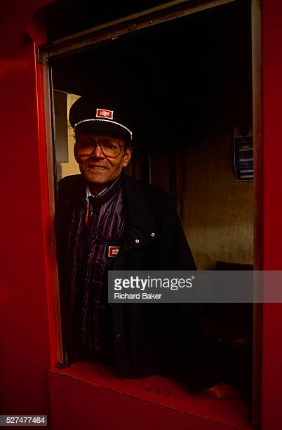 Portrait of a British Rail employee stands at the gate of a platform at Victoria station. Wearing the old uniform of that rail company. British...
