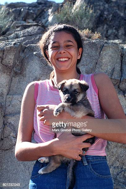 Portrait of a brownhaired teen girl as she holds a puppy and smiles Juarez Mexico late 1980s She wears blue jeans and a pink cutoff tshirt