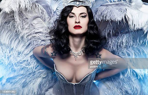 Portrait of a burlesque diva in a blue bustier and feathers