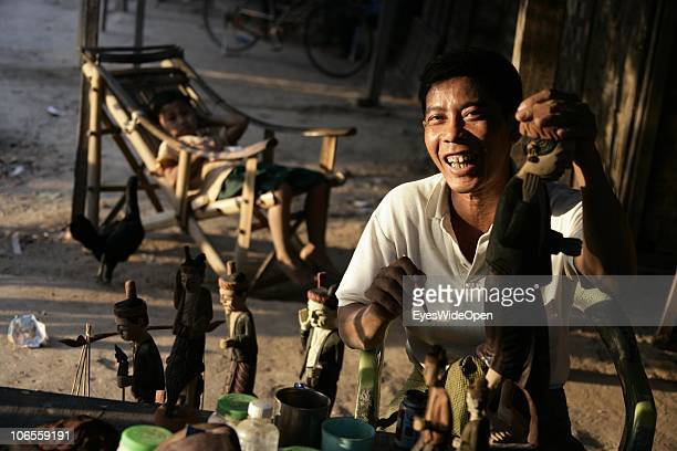 Portrait of a burmese male wood Carver U Min is painting his wooden figures puppets in the historical temple area of Bagan on Jan 18 2007 in Bagan...