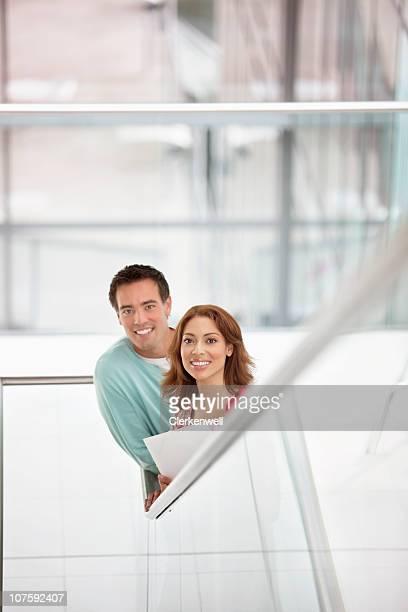 portrait of a business couple at staircase in office - 30 39 jaar stockfoto's en -beelden